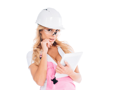 attractive handy woman in pink uniform and glasses standing with digital tablet isolated on white