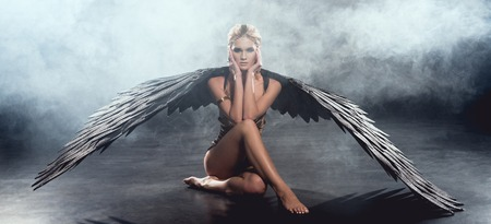 beautiful sexy woman with black angel wings sitting, touching face and posing on dark background