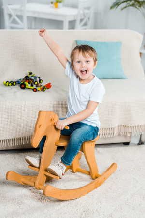 adorable excited preschooler boy riding rocking horse and gesturing with hand at home