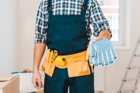 cropped view of handyman holding gloves in hand Stockfoto