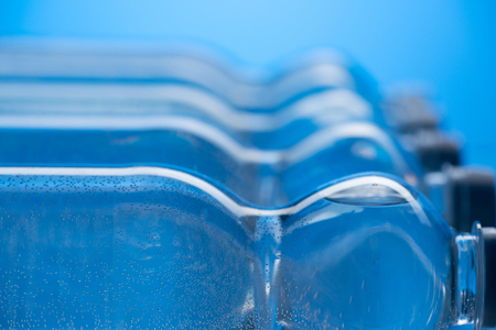 close up of plastic water bottles with bubbles in row on blue background
