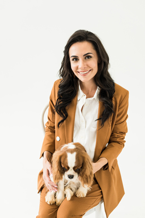 Glad brunette woman in brown suit holding dog and smiling isolated on white Stock Photo