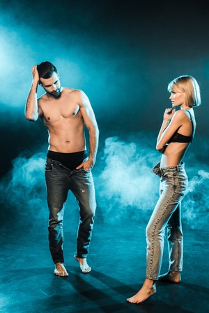 shirtless man and sensual woman posing on blue smoky background