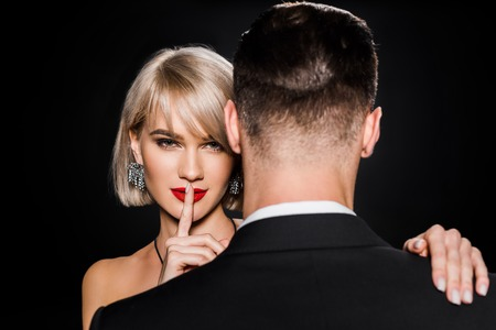 beautiful blonde woman showing silence symbol while standing with boyfriend isolated on black