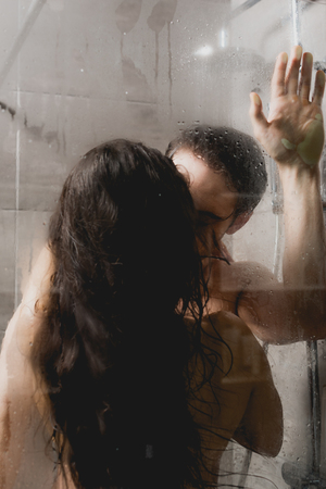 selective focus of naked man and attractive woman kissing in shower cabin