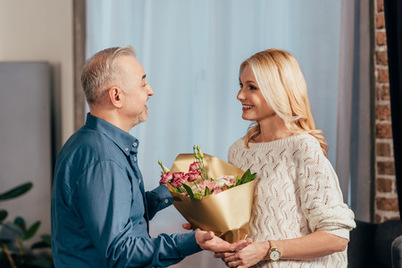 happy man smiling while giving flowers to attractive wife at home