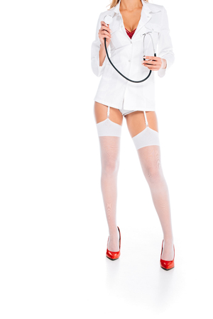 cropped view of nurse in short coat, stockings and red shoes holding stethoscope on white background