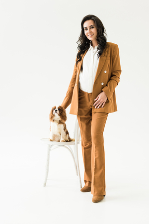 Full length view of pregnant woman in brown suit with dog on white background Stock Photo