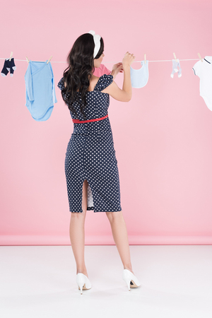 Back view of woman in dotted dress hanging out baby clothes on clothesline on pink background Archivio Fotografico - 118998591