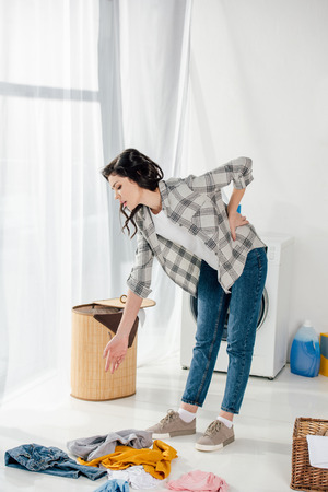woman standing near baskets and holding backache in laundry room