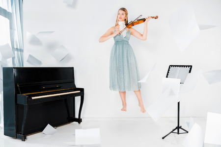 floating girl in blue dress playing violin near piano with sheets of paper in air