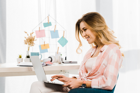 Smiling blonde woman in checkered shirt typing on laptop keyboard