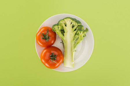 top view of red tomatoes near organic broccoli on white plate isolated on green