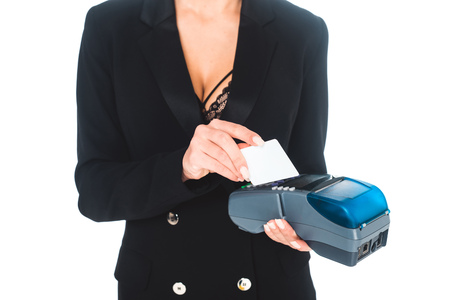 cropped view of businesswoman in black formal wear doing transaction by terminal with credit card isolated on white Zdjęcie Seryjne