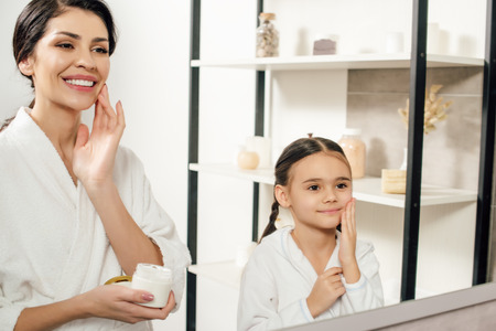mother and daughter in white bathrobes applying cosmetic cream in bathroom Stock Photo