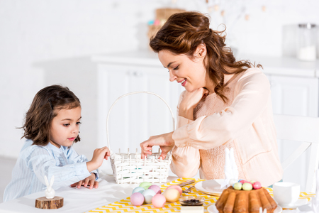 Mother and daughter putting easter eggs in wicker basket in kitchen