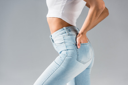 Cropped shot of sexy girl in jeans with hands in pockets isolated on grey