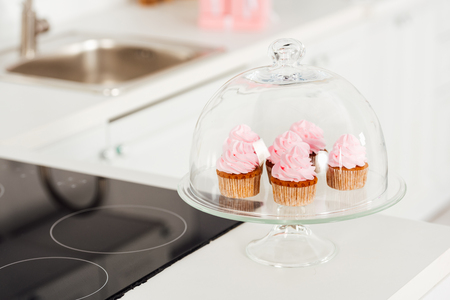 selective focus of glass stand with pink cupcakes and dome near induction cooker in kitchen Stock Photo