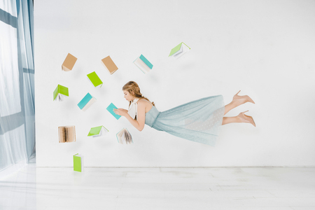 floating girl in blue dress reading book in air on white background Stock fotó