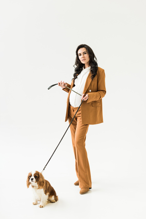 Stylish pregnant woman in brown suit standing near dog on white background
