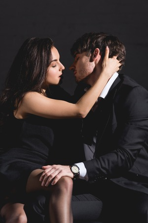 man in suit and woman in black dress sitting and kissing on couch on black background