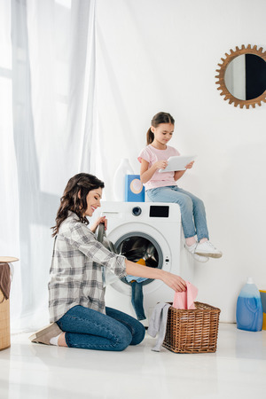 daughter in t-shirt sitting on washer with digital tablet wile mother in grey shirt taking clothes from basket in laundry room