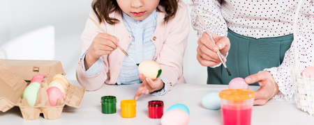 Panoramic shot of mother and daughter painting easter eggs