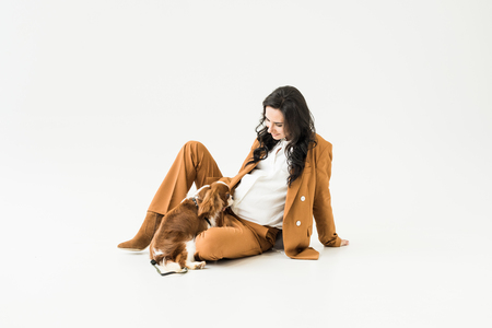 Stylish pregnant woman in suit sitting on floor and looking at dog on white background