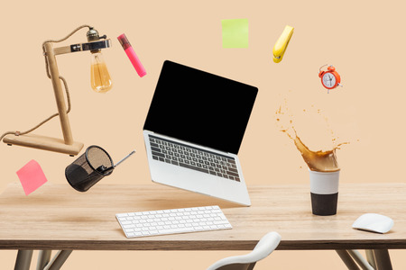laptop with blank screen, lamp, empty sticky notes and stationery levitating in air above workplace with thermomug with coffee splash  on table isolated on beige Banco de Imagens