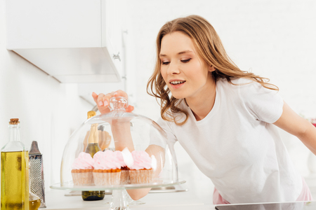 beautiful smiling girl in pajamas holding dome from glass stand with pink cupcakes in kitchen 写真素材
