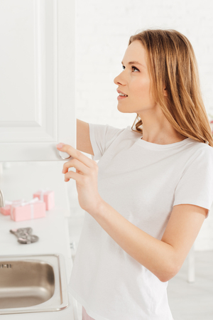 selective focus of beautiful girl in pajamas opening cupboard in kitchen Stock Photo