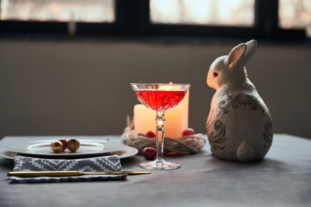 selective focus of decorative bunnie, plates with eggs, wine in crystal glass, candles on table at home