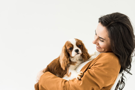 Excited brunette woman in brown jacket holding dog with smile isolated on white