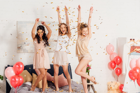 beautiful multicultural girls in nightwear dancing and having fun under falling confetti during pajama party