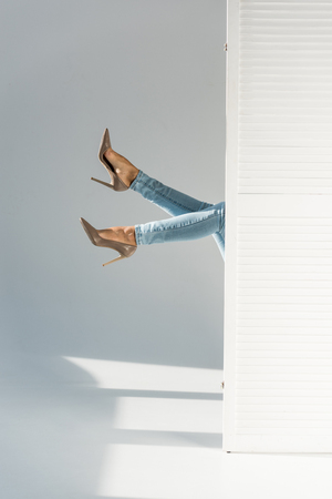 Partial view of woman in jeans and high-heeled shoes on grey background Stock Photo
