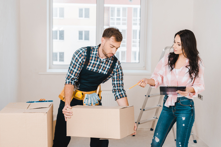 attractive woman pointing at box in hands of handyman