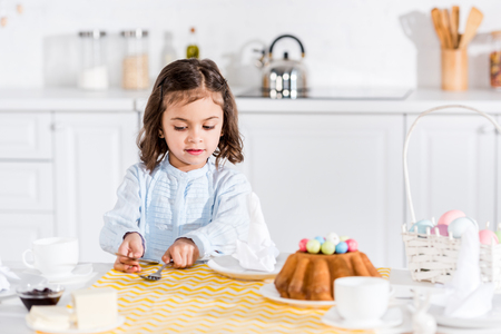 Cute preschooler kid sitting at table in kitchen in easter