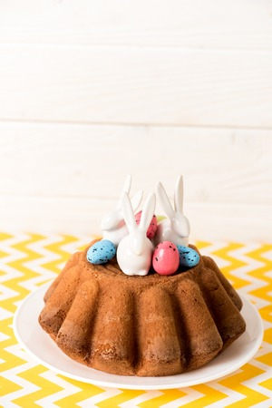 Easter bread with painted quail eggs and ceramic rabbits on yellow surface Stock Photo