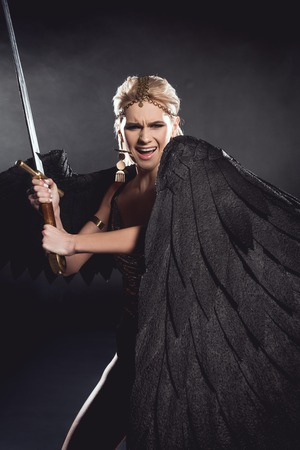 beautiful angry woman in warrior costume with angel wings holding sword and posing on black background 版權商用圖片