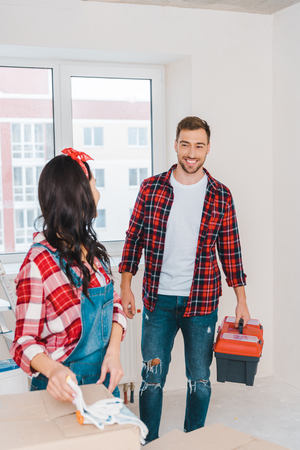 selective focus of cheerful man looking at woman while holding toolbox