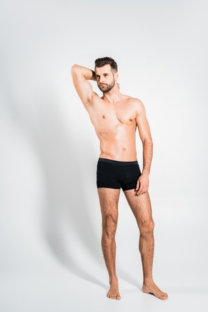 handsome shirtless man in black underwear posing on grey