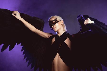 schöne Frau in Spitzenmaske und schwarzen Engelsflügeln posiert mit ausgestreckten Händen auf violettem Hintergrund