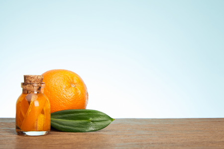 Glass bottle and ripe orange with green leaf on wooden surface