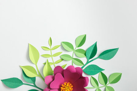 top view of pink paper flower and green plants on grey background