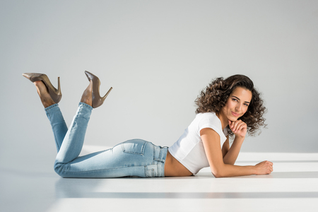 Sensual young woman in high-heeled shoes lying on grey background