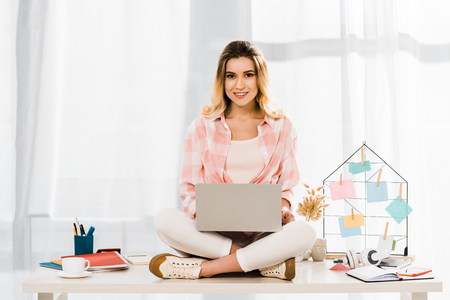Smiling woman in checkered shirt sitting on table with laptop Stock Photo
