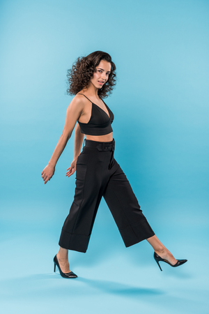 Curly young woman in black clothes walking on blue background