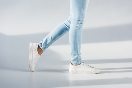 Partial view of woman in blue jeans and white shoes on grey background