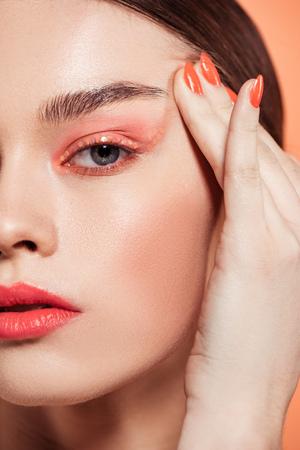 schöne stilvolle junge Frau mit Glitzer-Make-up, die isoliert auf Koralle in die Kamera schaut Standard-Bild