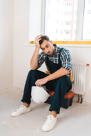exhausted handyman sitting on toolbox and holding helmet Stockfoto